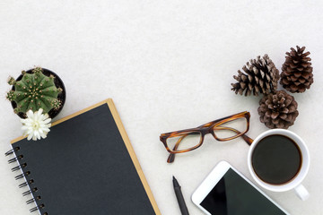 Flat lay photo of office desk with smartphone, eyeglasses and notebook with copy space background
