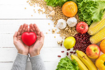 Woman hands showing red heart ball with healthy food aside