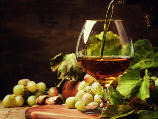 Cognac Pour In Glass, Grapes And Vine, Vintage Wood Background, Selective Focus