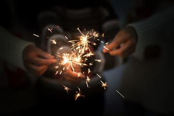 Bright festive Christmas or New Year sparkler in hand toning, showing group of friends having fun.
