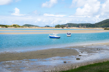 Ngunguru Harbour at low tide with boats moored in the river estuary near the sandspit - in Northland, New Zealand, NZ