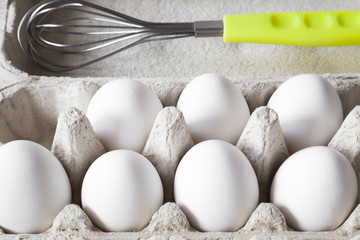 White eggs in the eggs box with whisk. Food concept.