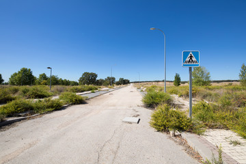 overgrown street with crosswalk sign in abandoned urbanization, near Guadalajara city, Spain, Europe