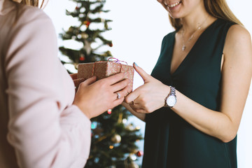 Happy and surprised woman receiving a gift. Merry Christmas