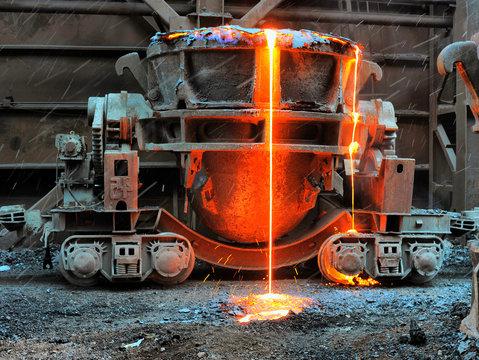Old slag disposal pots mounted on railway platforms in blast furnace workshop
