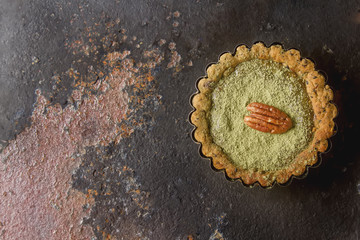 Green tea vegetarian pie match with nuts and mint. Dark background. Selective focus. Top view