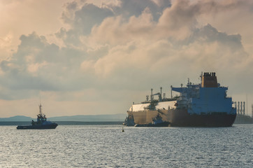 LNG TANKER- The big tanker maneuveres in the harbor secured by tugs