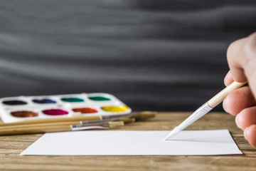 Artist painting a picture with paint brush on white sheet. Art concept.