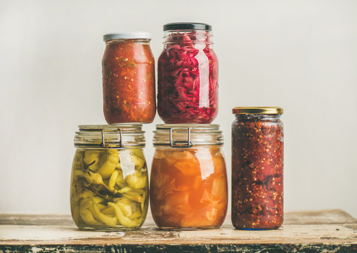 Autumn seasonal pickled or fermented colorful vegetables in glass jars placed in stack over vintage kitchen drawer, white wall background. Fall home food preserving or canning