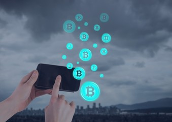 Bitcoin icons and hand holding phone