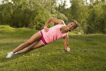 young beautiful girl engaged in fitness and gymnastics in the park. morning gymnastics.