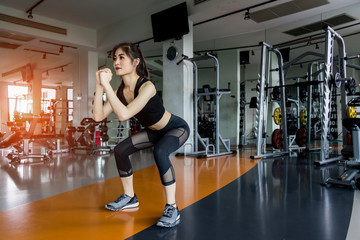 Woman exercise doing squat workout at gym fitness center, athlete muscle bodybuilder strong concept