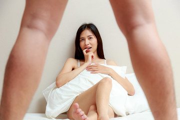 Surprised shocked Asian woman setting in a bed looking to her boyfriend, coulpe and sexual concept