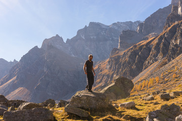 Young adult man hiker climb down a rock on mountain in sunny autumn day on Alps in Italy outdoor.