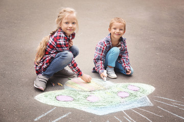 Little children drawing alien spaceship with chalk on asphalt