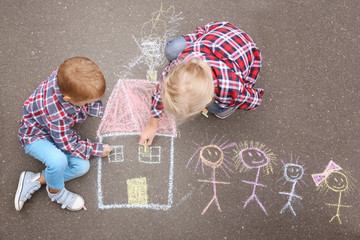 Little children drawing house and family with chalk on asphalt