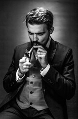 black and white portrait of bearded  gentleman in a suit lights acigar