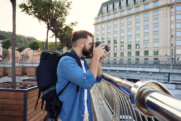 Young male tourist taking photo outdoors