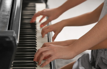 Little girl playing piano with teacher indoors, closeup