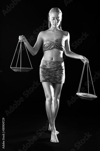 Beautiful young woman with amazing bodyart as Libra on dark