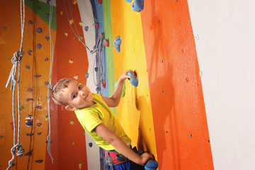 Adorable little boy climbing on wall in gym