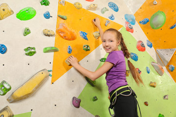 Cute little girl climbing on wall in gym
