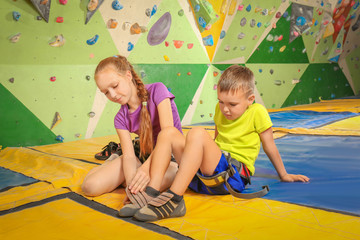 Adorable girl helping little brother to put on shoes in climbing gym