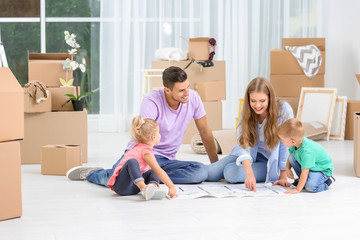 Family studying plan of their new home while sitting on floor