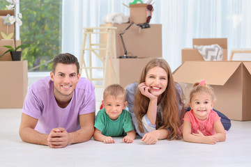 Happy family lying on floor near moving boxes in their new house