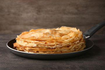 Frying pan with stack of delicious thin pancakes on wooden table