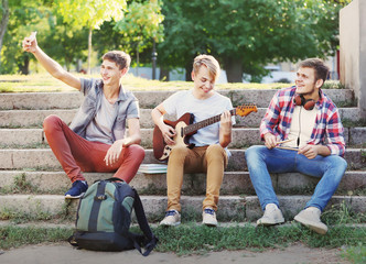 Teenager musicians taking selfie while sitting on steps outdoors