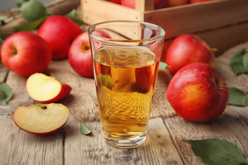 Glass with fresh apple juice on wooden table