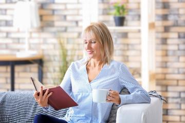 Beautiful mature woman reading book at home