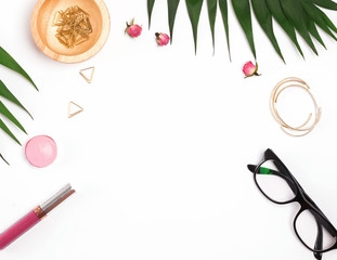 Feminine accessories and green palm leaves on the white background