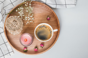 Cozy morning still life with coffee, candle and flowers on the wooden tray