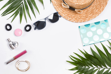 Vacation flat lay with straw hat, palm leaves and other