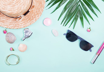 Feminine vacation accessories and green palm leaves