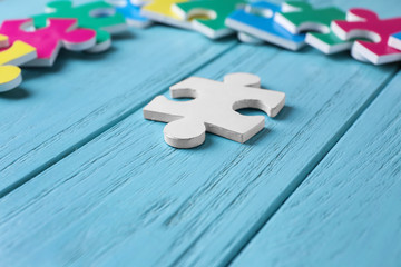 White puzzle on color wooden background. Concept of autism