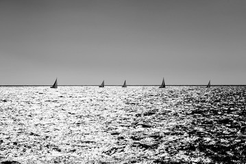 Small sailing racing boats in a sea of silver as the sun stands low.Monochrome silver effect applied, symmetric composition