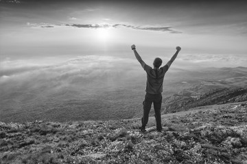 Hiker standing on a hill with raised hands. Black and white