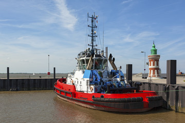 Red tugboat moored next to the historic Pingelturm lighthouse at port of Bremerhaven