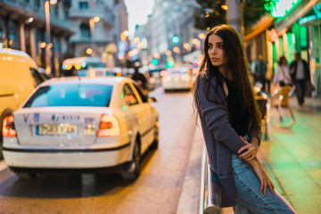 Young delicate model posing at street