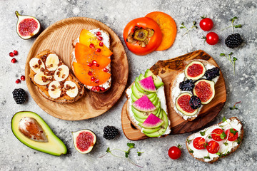 Healthy breakfast toasts with avocado, peanut butter, banana, chocolate granola, cream cheese, figs, blackberry, persimmon, pomegranate, chia seeds. Top view, overhead