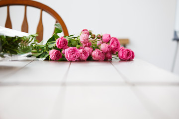 Picture of bouquet of pink peonies on white wooden table