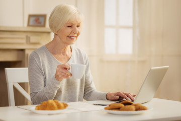 Great day. Cheerful woman expressing positivity and holding cup while sitting at kitchen