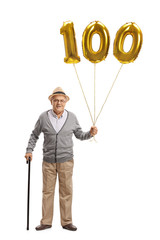 Mature man holding a golden number hundred balloon and a cane