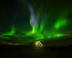 Night photo. Northern lights above the house in old traditions with grass on the roof. Iceland.