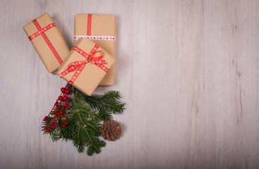 Christmas gift and ornaments with pine tree and cone over a wood background