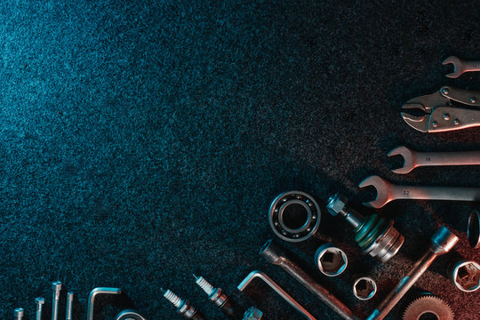 Bearings, wrenches, bolts on a dark background. view from above. Flat design. Automotive subjects. Copy space.