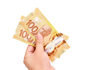 A hand with Canadian 100 Dollar, isolated on white background